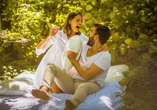Morning pillow fight in nature. Couple relationship. Morning pillow fight in nature. Young couple stock images