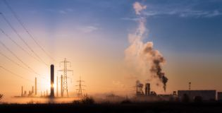 Morning Pollution 3. Country sunrise scene with industrial buildings, pollution and fog. Greenpeace and Earth day. Plastics production and smoke. Oil producing royalty free stock image