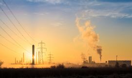 Morning Pollution 1. Country sunrise scene with industrial buildings, pollution and fog. Greenpeace and Earth day. Plastics production and smoke royalty free stock images