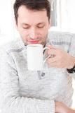 Morning portrait of handsome guy smelling and holding coffee cup. Wit eyes closed at his home indoors, domestic atmosphere stock photography