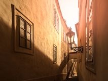 Morning Prague scene. Sunlit and long shadows on the wall with gas street lamp, Thunovska Street, Lesser Town, Prague. Czech Republic Stock Photo