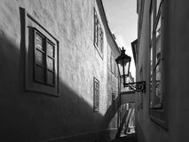 Morning Prague scene. Sunlit and long shadows on the wall with gas street lamp, Thunovska Street, Lesser Town, Prague Stock Photos