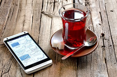 Morning red tea with smartphone Royalty Free Stock Images