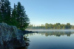 Morning Reflections on a Foggy Wilderness Lake Royalty Free Stock Photography