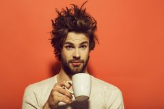 Morning refreshment of surprised man with cup of tea, coffee. Morning refreshment of surprised man with cup of tea or coffee has uncombed hair in underwear on stock photo