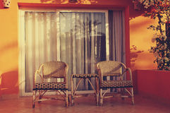 Morning on the resort. Two wicker chairs and a table against the window with exit to the balcony in the morning on the resort Stock Images