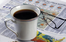 Morning Rituals - Hot Coffee And A Newspaper. A hot cup of coffee and a morning newspaper portray the morning ritual of waking up stock photography