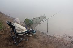 Morning on the river. Fisherwoman sleeps in a folding chair. Next to fishing gear on a foggy autumn morning on the river bank royalty free stock photos