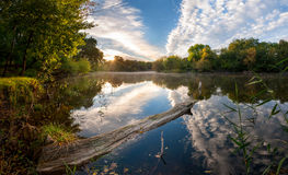 Morning on river with majestic clouds reflection in water. Beautiful landscape on morning river with majestic clouds reflection in water, sun rising over forest Stock Images