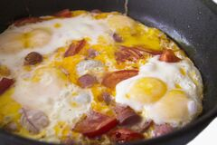 Morning roasted whole eggs on the black frying pan and with tomato and sausages