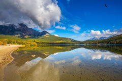 Morning in the Rocky Mountains, Canada. Pyramid Mountain and magnificent cumulus clouds reflected in the smooth water of Pyramid Lake. Morning in the Rocky royalty free stock photo