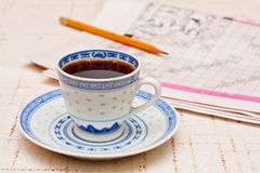 The morning routine. A cup of coffee and a newspaper with a pencil on it Royalty Free Stock Images