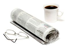 Morning Routine. Daily paper with coffee and a pair of glasses royalty free stock image