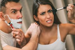Morning Routine. Beautiful young couple having hectic morning habits in front of their bathroom mirror. Man shaving and his girlfriend makeup. Selective focus Stock Photos