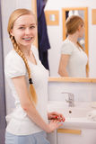 Happy woman reflecting in mirror. Morning routine concept. Happy woman standing in bathroom, reflecting in mirror stock images