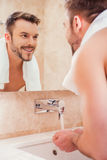Morning routine. Handsome young man washing hands in bathroom while standing in front of the mirror Royalty Free Stock Photos