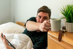College student waking up and having coffee in bed stock images