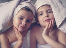 Morning routine. Two little girls. Two cute little girls with towels on the head posing to the camera. Beauty staffs Stock Photography