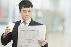 Morning routine of young businessman holding and drinking coffee and reading newspaper Stock Images