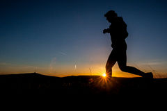 Morning run. Silhouette of a man running at sunrise Stock Images