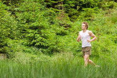 Morning run: Young man jogging in nature. In sportive outfit Royalty Free Stock Images