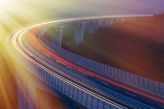 Morning rush hour. Blurred lights of vehicles driving on a tall viaduct with wind barriers, long exposure, sunlit with golden rays. Morning traffic Stock Photos