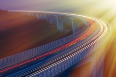 Morning rush hour. Blurred lights of vehicles driving on viaduct, long exposure, sunlit with golden morning rays. Transportation, on the road, connectivity and Stock Image