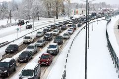 Morning rush hour. Riga, Latvia - November 04, 2016: Typical scene during morning rush hour in a traffic jam with rows of cars. First snowy day. Heavy snowfall Royalty Free Stock Photos