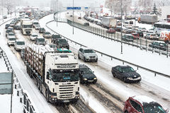 Morning rush hour. Riga, Latvia - November 04, 2016: Typical scene during morning rush hour in a traffic jam with rows of cars. First snowy day. Heavy snowfall Royalty Free Stock Image