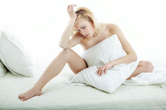 Morning sadness. Sad woman sitting on the bed at the morning Stock Image