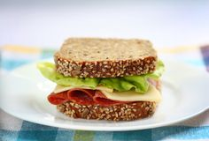 Morning sandwich. Sandwich made of healthy brown bread with seeds  lettuce italian salami and cheese Royalty Free Stock Photography