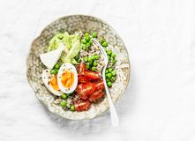 Morning savory breakfast bowl. Balanced bowl with quinoa, egg, avocado, tomato, green pea. Healthy diet food concept. Top view stock photo