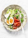 Morning savory breakfast bowl. Balanced bowl with quinoa, egg, avocado, tomato, green pea. Healthy diet food concept. Top view royalty free stock photo