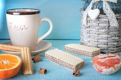 Morning scene with cup of tea or coffee, Dutch cookie stroopwafel, Delfts blue souvenir, on blue table Royalty Free Stock Photo
