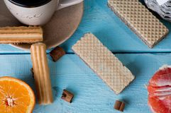 Morning scene with cup of tea or coffee, Dutch cookie stroopwafel, Delfts blue souvenir, on blue table Stock Photo