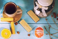 Morning scene with cup of tea or coffee, Dutch cookie stroopwafel, Delfts blue souvenir, on blue table Royalty Free Stock Image