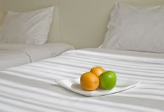 A morning scene in the hotel room bed. Plate of fresh fruits placed on the bed in the morning Royalty Free Stock Photo