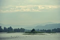 Morning scenery of the river and banks in a light haze with clouds in the high sky. River and banks in a light haze with clouds in the sky Royalty Free Stock Photos