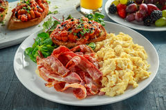 Morning Scrambled egg, bacon breakfast with beans in tomato sauce on toasted bread on white plate Stock Photos