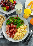 Morning Scrambled egg, bacon breakfast with orange juice, milk, fruit, bread on white plate Stock Image