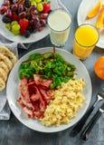 Morning Scrambled egg, bacon breakfast with orange juice, milk, fruit, bread on white plate.  Stock Image