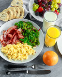 Morning Scrambled egg, bacon breakfast with orange juice, milk, fruit, bread on white plate Royalty Free Stock Photography