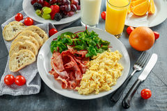 Morning Scrambled egg, bacon breakfast with orange juice, milk, fruit, bread on white plate Royalty Free Stock Photos