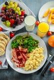 Morning Scrambled egg, bacon breakfast with orange juice, milk, fruit, bread on white plate.  Royalty Free Stock Photos