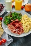 Morning Scrambled egg, bacon breakfast with orange juice, milk, fruit, bread on white plate.  Stock Photos