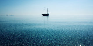 Morning sea with boat on the horizon. Aged photo. Stock Photos