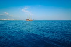 Morning sea with boat on the horizon. Aged photo. Sailing ship profile. Toned image. Sunbeams on the sea surface. Calm Sea with a Sailing Vessel. Cirali Royalty Free Stock Images
