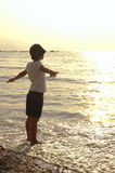 Morning on the sea child arms outstretched basking in the sun Stock Photography