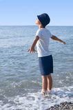 Morning on the sea child arms outstretched basking in the sun Stock Images