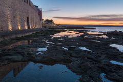Morning by the sea by the city wall Royalty Free Stock Image